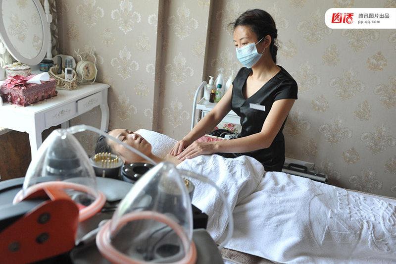 图为2013年8月11日,杭州,女催乳师胡敏娟在给一位客人进行乳房按摩催乳