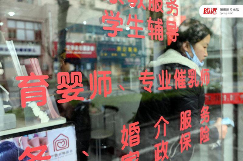 图为2016年3月9日,上海一家机构门玻璃上显示,提供专业催乳师服务的广告