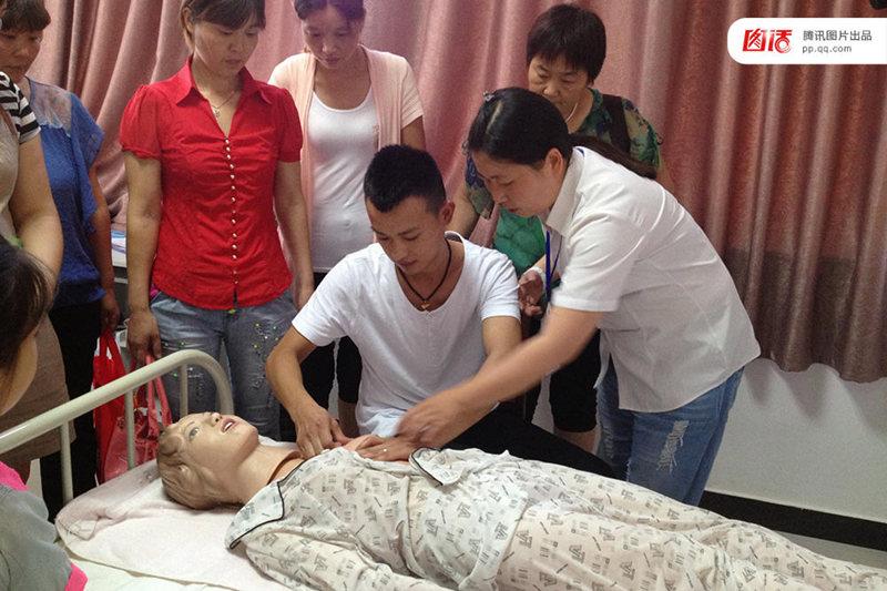 图为2013年7月17日,河南濮阳,男催乳师杨军在教师指导下学习催乳技巧