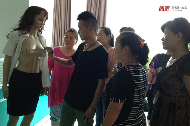 图为2013年7月17日,河南濮阳,催乳师杨军正在硅胶女模特上接受老师培训