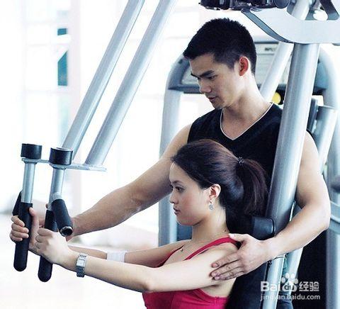健身房私人教练在给女会员指导器械训练