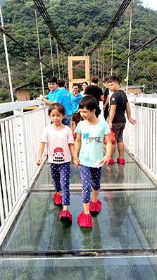 两个孩子携手走过玻璃栈桥.jpg