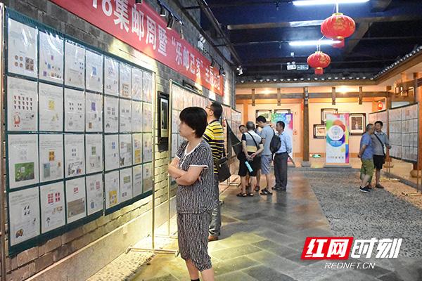 邮迷们仔细欣赏展出的邮票。.jpg