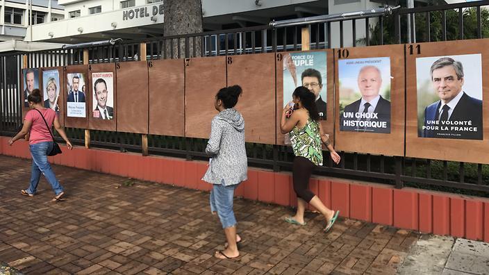 在法国太平洋属地新喀里多尼亚首府努美阿,人们前往投票站准备投票。
