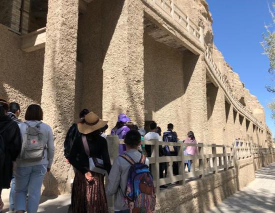 游客参观敦煌研究院莫高窟