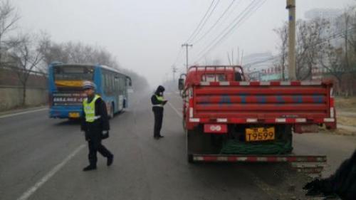 环境监察人员检查路上行驶的大货车