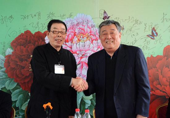 陈晓光(右)与新当选的会长宋小明握手