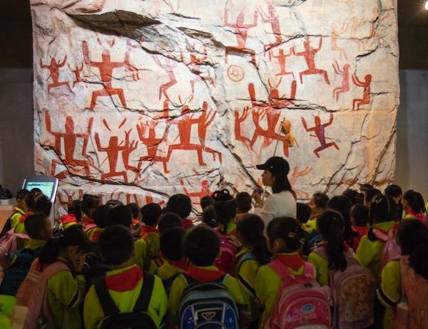 """""""左江花山岩画文化景观""""入选《世界遗产名录》,填补了中国岩画类世遗项目的空白。图为学生们在广西民族博物馆参观花山岩画。宋明昌摄影 (2).jpg"""