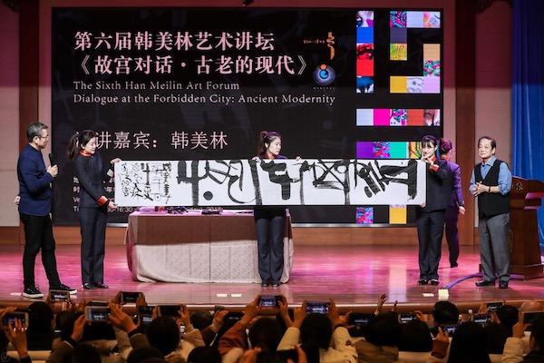 韩美林在演讲过程中展示书法作品.jpg